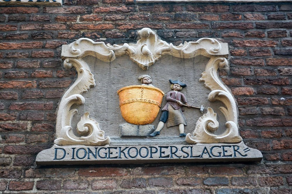 Signs like these used to be put over shops. They included a picture of what the shop was so those who could not read knew what to expect inside. In this instance we see a bell maker!
