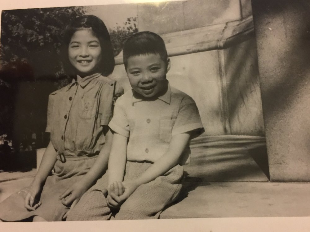 Cynthia Yee , wearing her Brownie Troop 52 uniform, and her cousin, Albert Yee, at the Boston Commons Frog Pond monument c. 1956