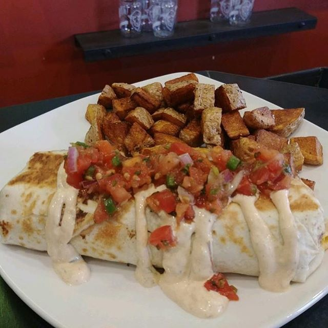 Cozy little breakfast burrito for your brunch today: fluffy flour tortilla filled with ham, cheddar, green chiles, and topped with chipotle sour cream and pico de gallo.