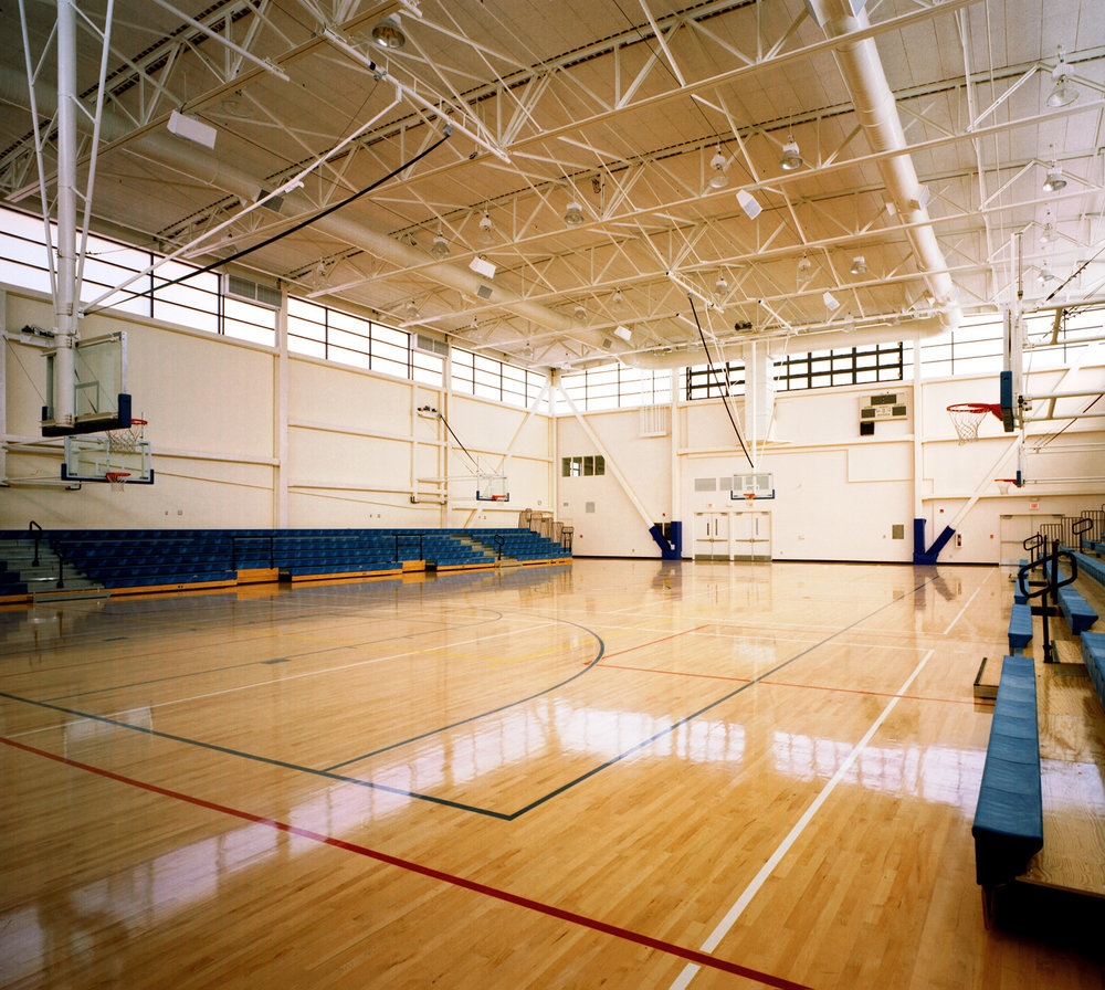 - The gymnasium interior is illuminated in the daytime by high translucent clerestory glazing. This glazing, on the East and West ends of the building are operable, providing natural ventilation.