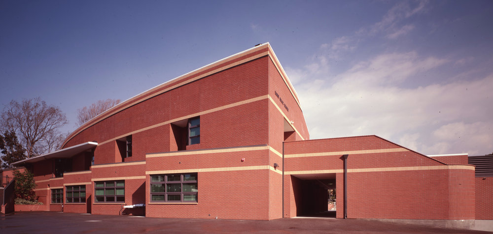 - The building as seen from the athletic field area, with a courtyard access, beneath the second level, on the right.