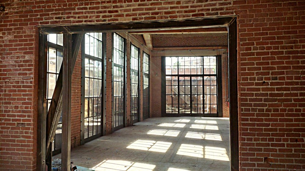 - Interior view near the end of construction showing the new steel storefront system