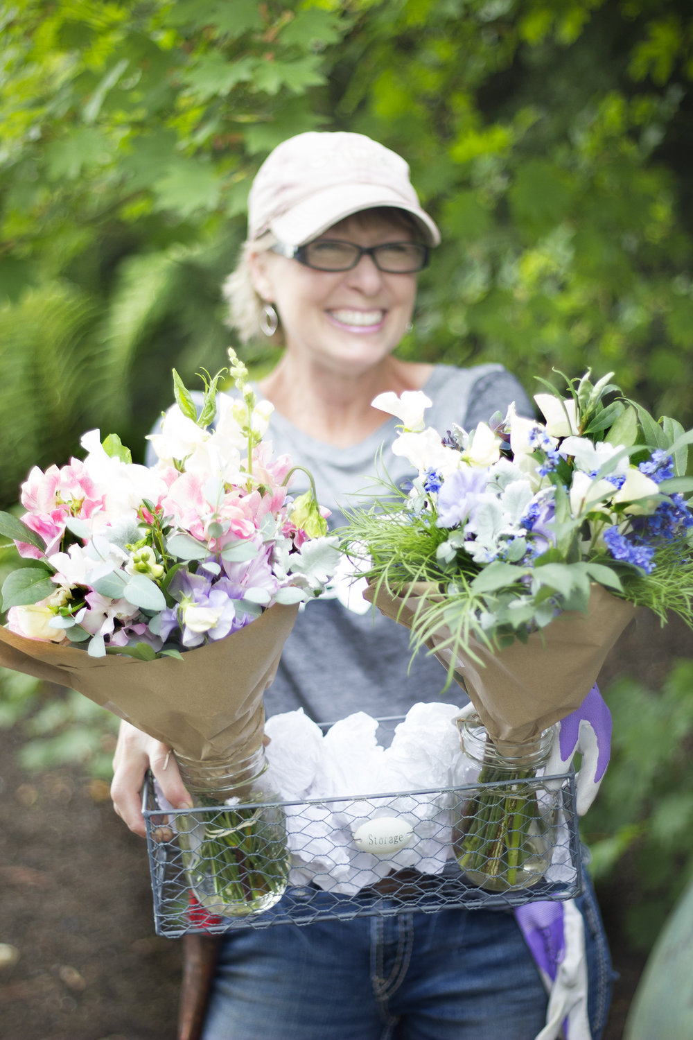 Gwen holding sweet pea bouquets grown from our onsite flower farm 'Scattered Seeds…a Flower Farm'