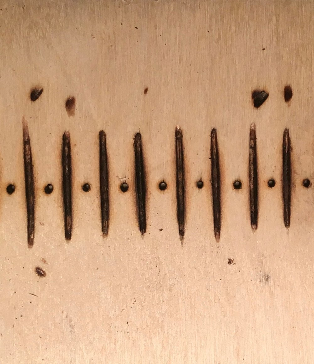 Image: Dots and dashes cut and burned into wood to create a loom's heddle