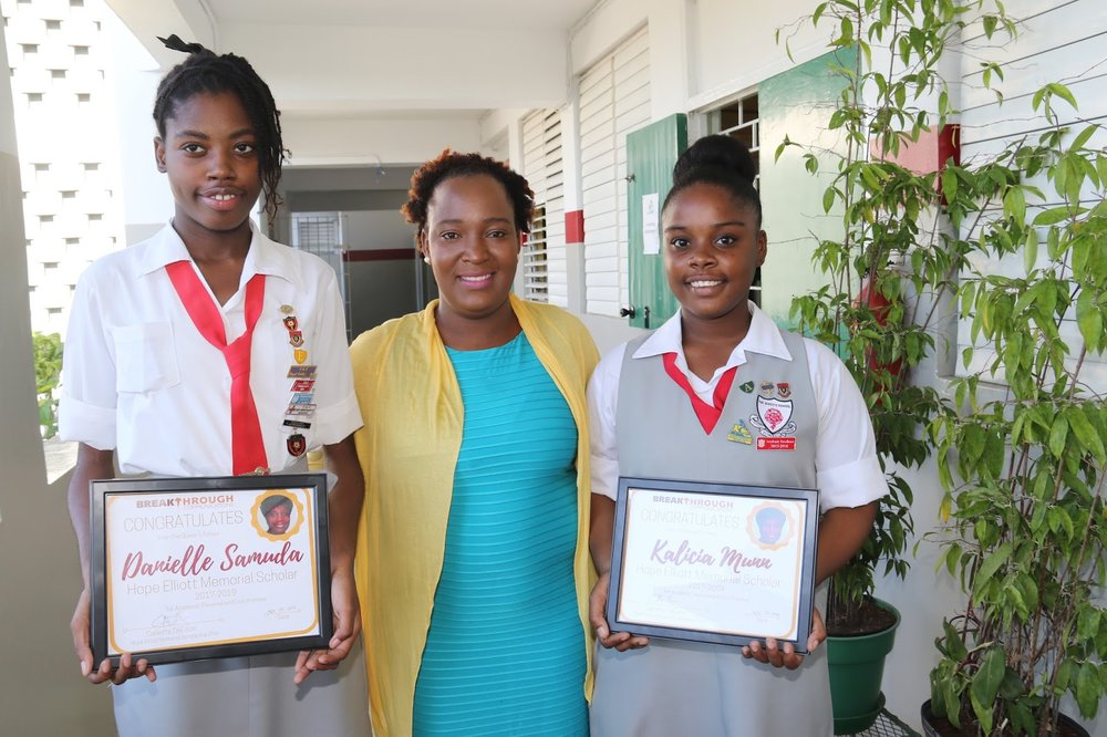 Hope Elliott Memorial Scholarship 2017-2019 awardees at The Queen's School: sixth-former Danielle Samuda (left) and fourth-former Kalicia Munn (right) stand proudly with guidance counselor Shallimar Reynolds after their special devotion presentation on Monday, November 20, 2017.
