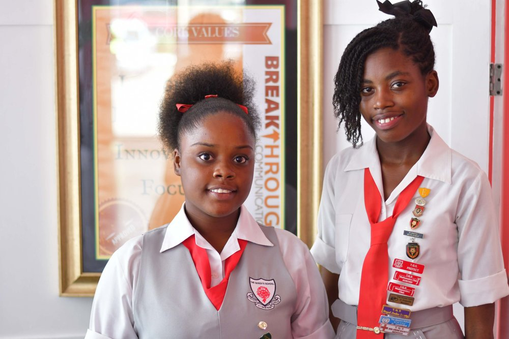 """Hope Elliot Memorial Scholarship recipients Danielle Samuda (left) and Kalicia Munn (center) pause for a photo opportunity following an inspirational """"Powerful Women Luncheon"""". The luncheon which was held on Wednesday, April 4 at the Spanish Court Hotel saw women from corporate Jamaica sharing their experiences with The Queen's School scholars."""