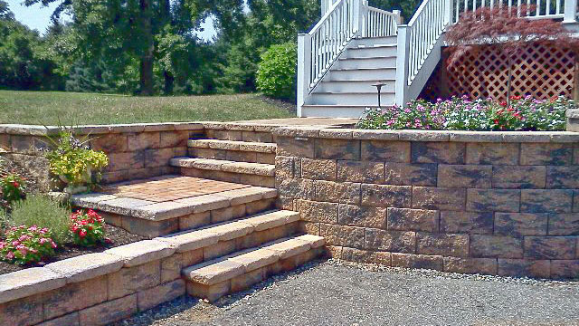 Segmental Retaining Walls - Tame that hillside with a stone retaining wall, create a beautiful plating area with a freestanding wall, or have a nice place to sit around your fire pit with a sitting wall.