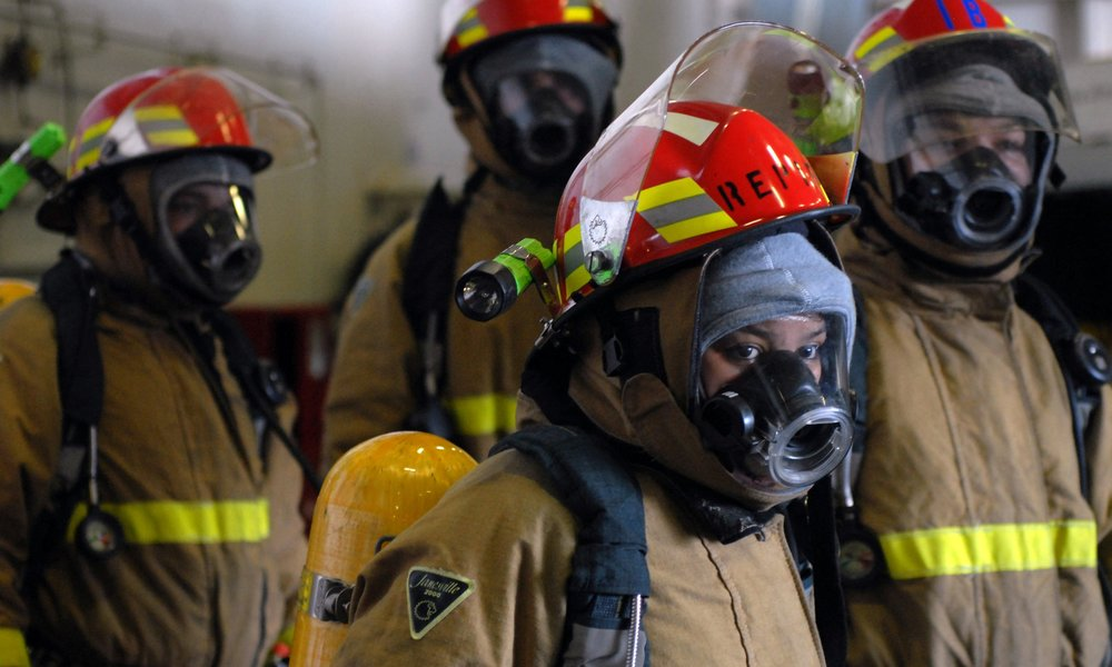 US_Navy_081107-N-1635S-004_Fully_dressed_out_in_firefighting_gear,_Reactor_Department_personnel_stand_by_for_orders_during_a_nuclear_power_mobile_training_team_(NPMTT)_drill_aboard_the_Nimitz-class_aircraft_.jpg