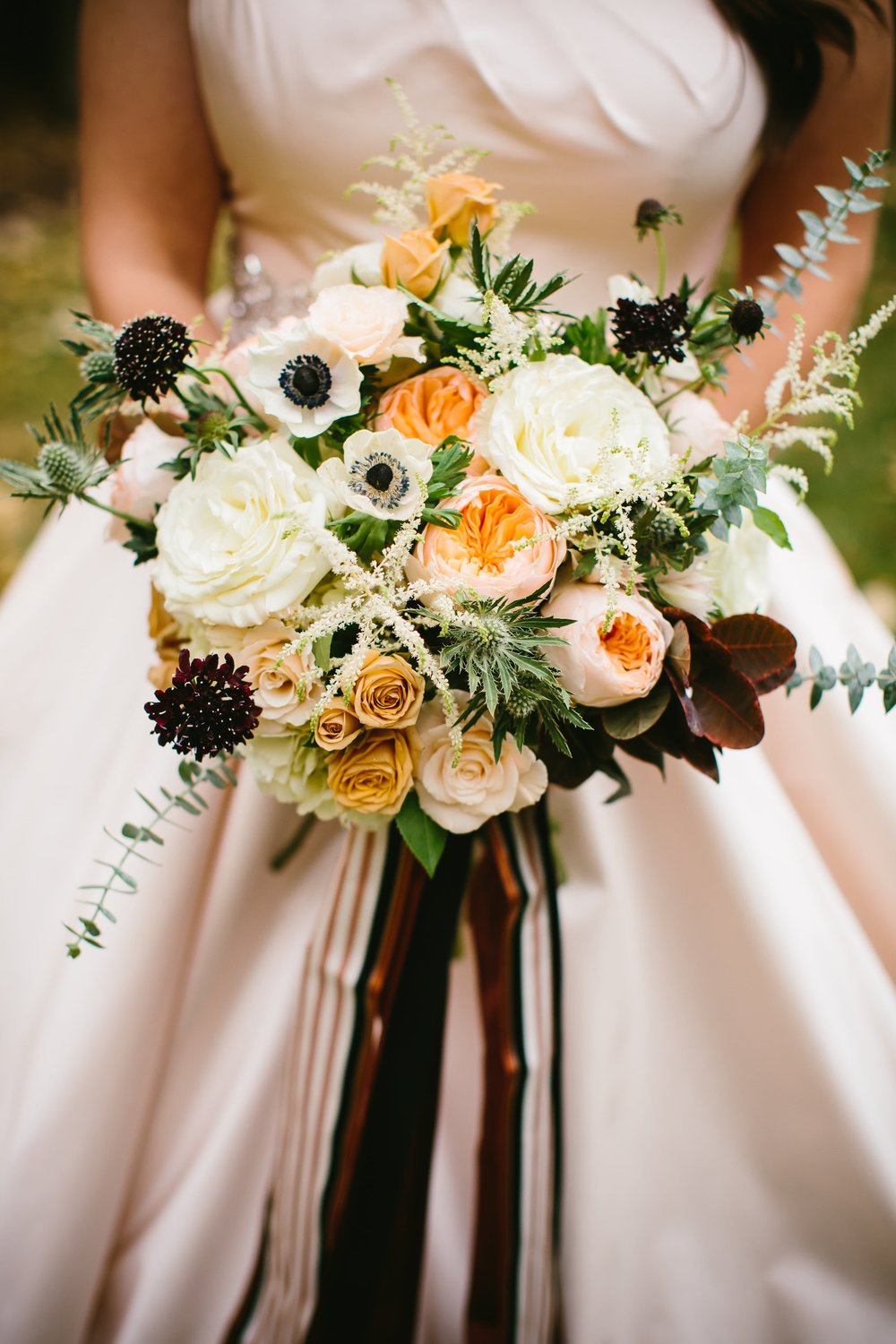10 Tanya's bouquet by Lily and Co. included ranunculus, anemones, roses, eucalyptus, black dahlias, and hydrangeas, as well as magnolia and Japanese maple leaves
