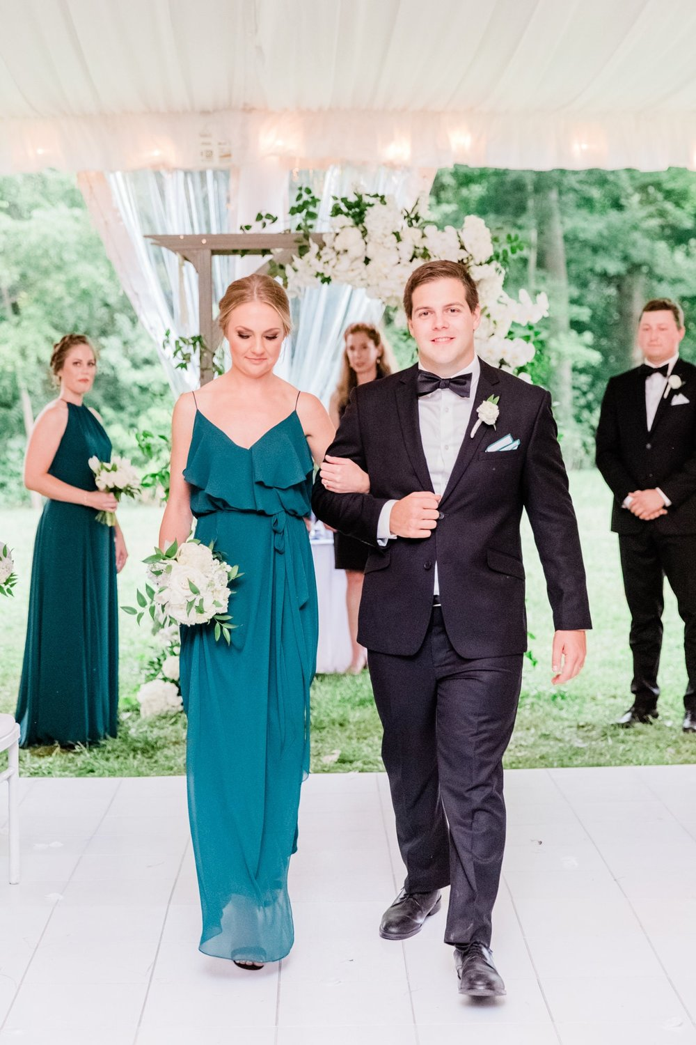 Bridesmaid and groomsman walking down the aisle in Nouvelle Amsale Bridesmaids