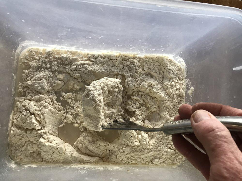 Using a potato masher to mix the sponge.