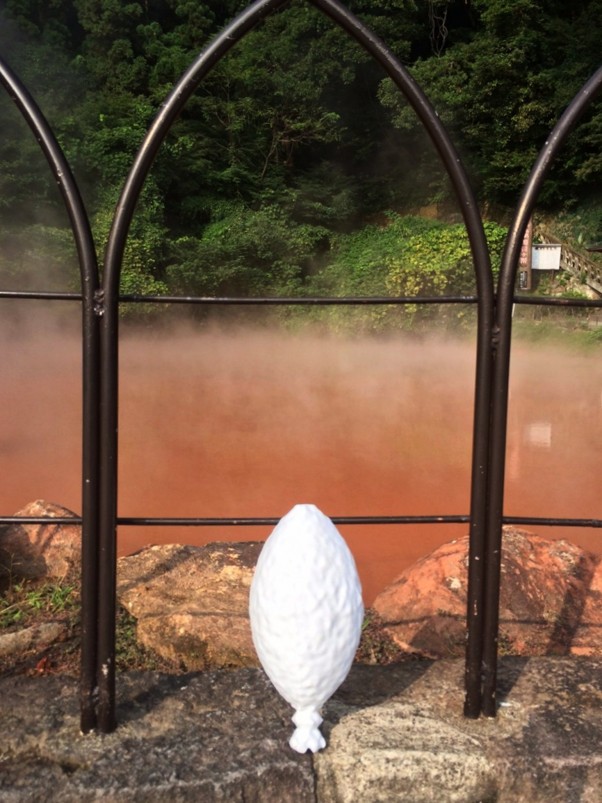 """Stanley"", our 3D printed model of an SSV1, in front of   Chinoike Jigoku. Translating to Blood Pond Hell, this geothermal hot spring in Beppu, Japan is where the first SSV was discovered. It is only one of the geothermal hot springs around the world where many more SSVs and similar viruses have been found."