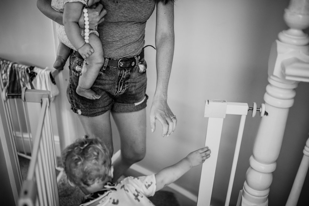 A mother walks down the stairs holding a baby in her arms and a toddler in front of her during this day in the life photo session in Yeovil, Somerset.