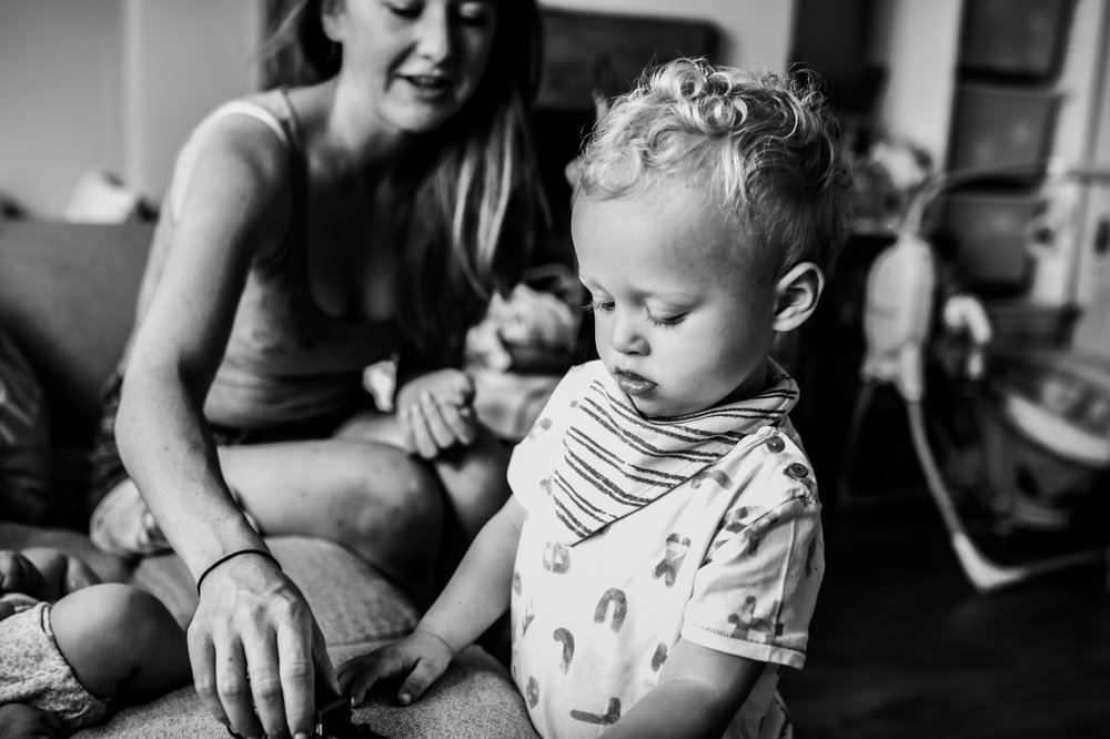 Mother and toddler son sit on their sofa playing with his toys during this day in the life photo session in Yeovil, Somerset.