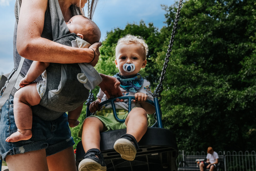 Toddler sits in a swing as his mother pushes him whilst holding her baby girl in a sling in their local park during this day in the life family photo session in Yeovil, Somerset.