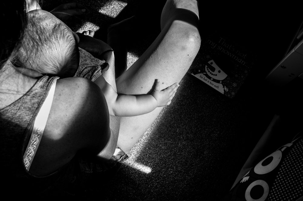 A black and white close up shot of a babys hand gipping her mothers leg as they sit on the floor of their bedroom.