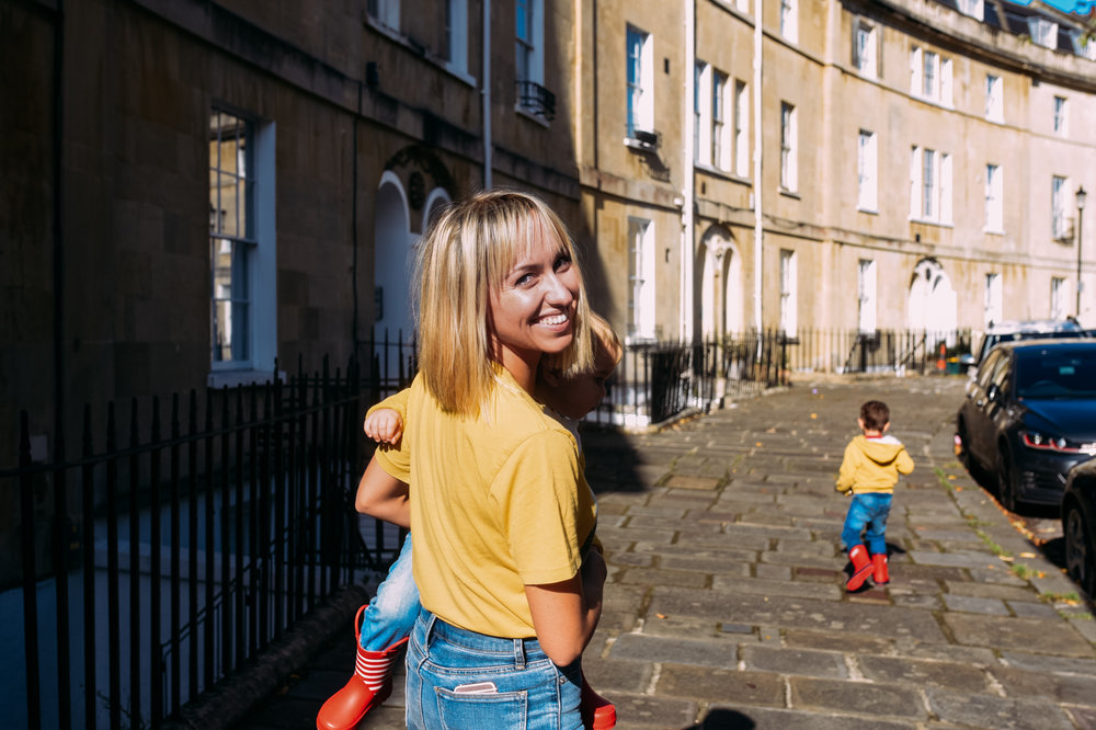 A mother walks along a pretty cresent in Bath holding her baby boy on her hip and smiling back at the camera over her shoulder.