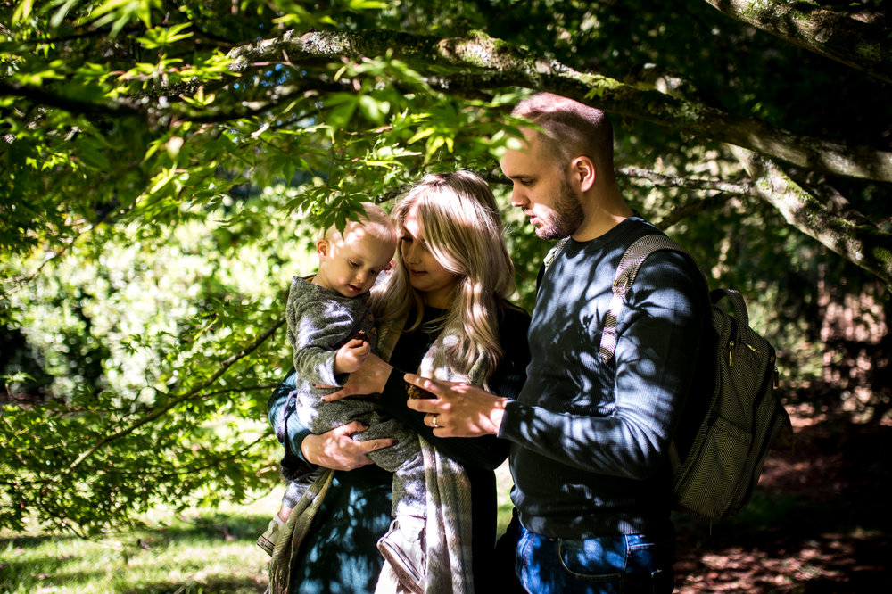 A young family of three stand under a tree during autumn family photo shoot at Westonbirt Arboretum.