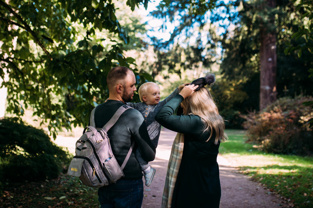 A toddler tires to put his hat on his mothers head as his father holds him during this autumnal family photo shoot at Westonbirt Arboretum.
