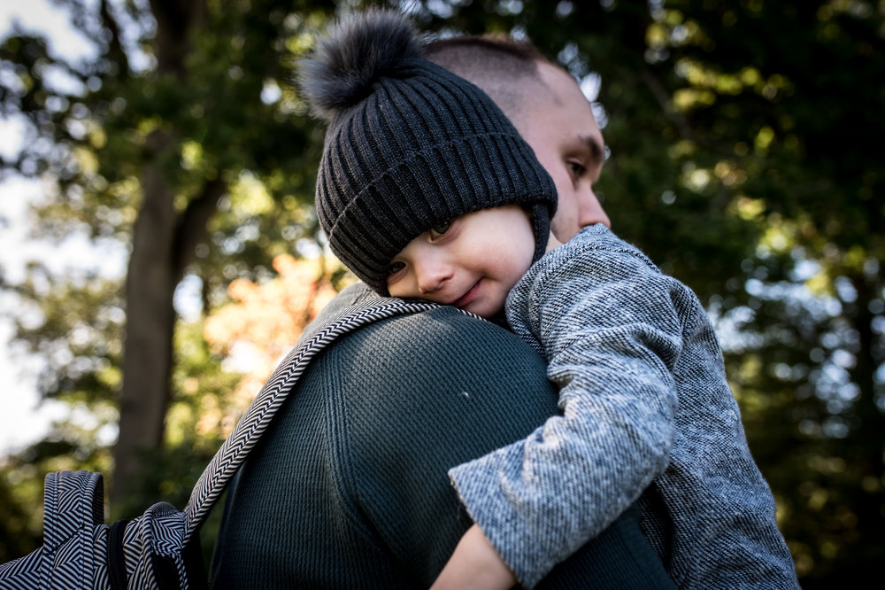 A side angle view of a baby cuddling into his Dad's shoulder as his father carries him through Westonbirt Arboretum.