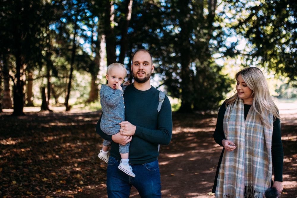 Two young parents walk through the trees holding their toddler son at Westonbirt Arboretum in Gloucestershire during this autumnal family shoot.
