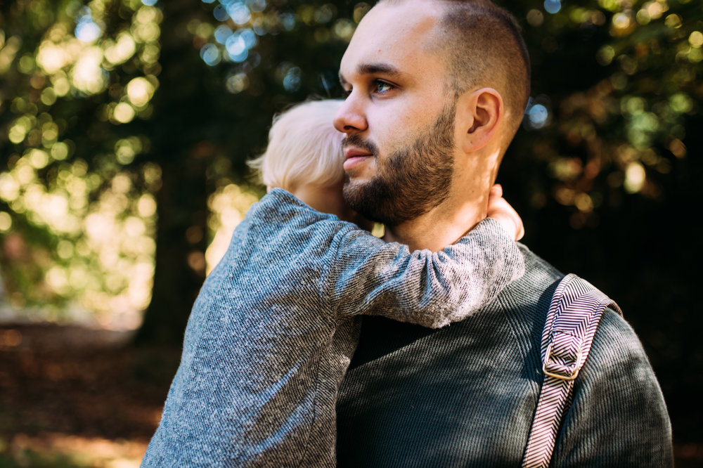 A baby boy puts his arms around his father as he is being held close during this autumn family photo shoot at Westonbirt Arboretum.