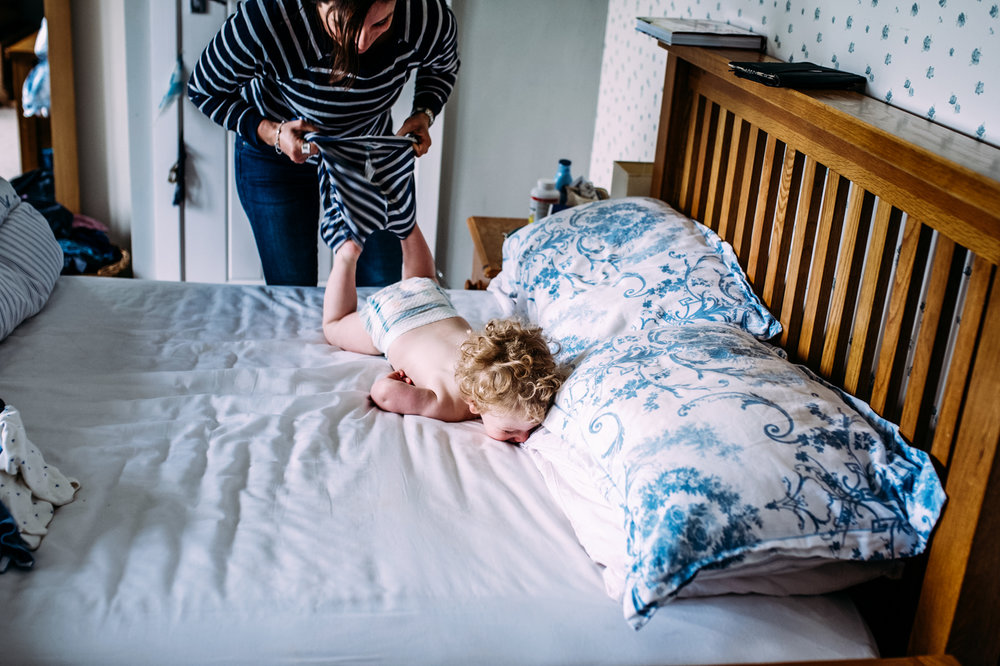 Mother playfully wrestling son on the bed while trying to get him dressed during in-home photo session in Bath.