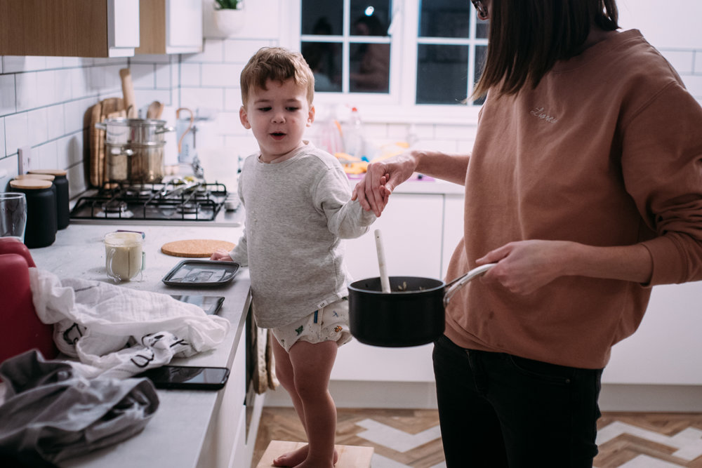 Mother holds sons hand in kicthen whilst they make dinner together during this documentary family photography session in Sussex UK.