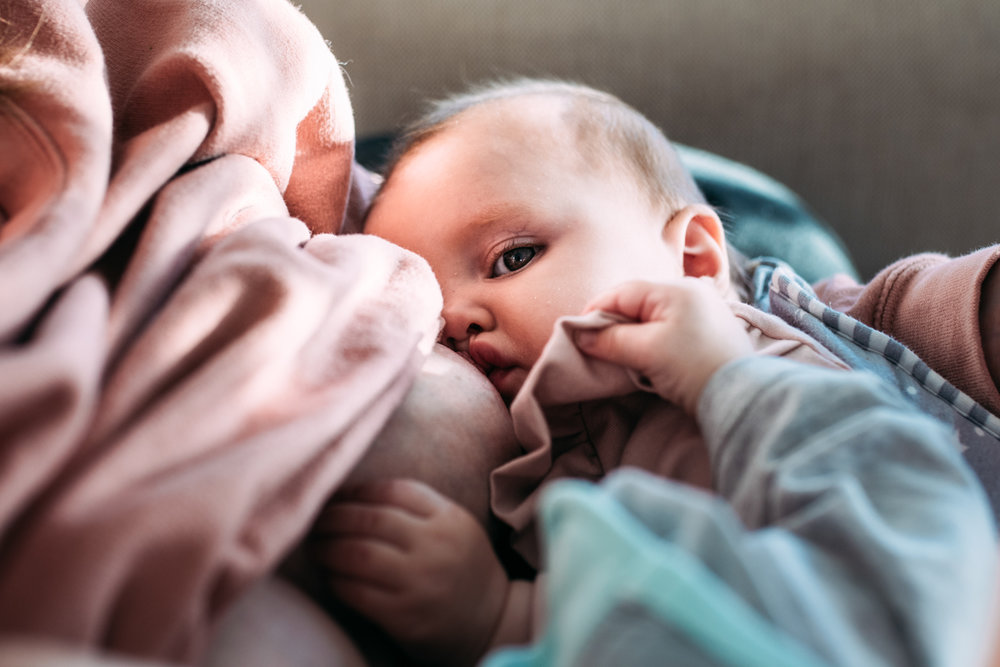 A close up shot of a baby girl breastfeeding during this documentary family photography session in Sussex UK.