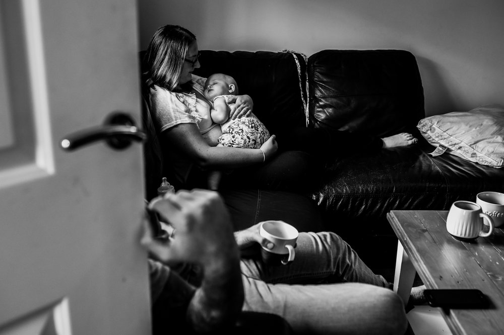 A shot through the door as her mother sits on her sofa holding her baby on her chest whilst her baby sleeps during this relaxed family photo session in Bath.