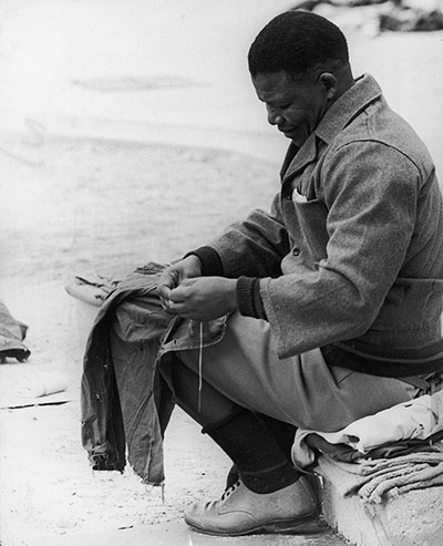 1966: Mandela sits and sews inmates' clothes in the yard of Robben Island prison