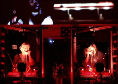 Stacey Collins and Ben in  Welcome to Nowhere ; Ben and Jessica Pagan on screen above.