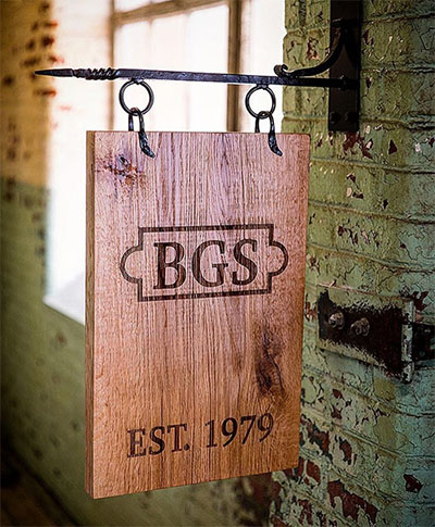 A hanging indoor business sign, engraved on 1 inch thick wood.