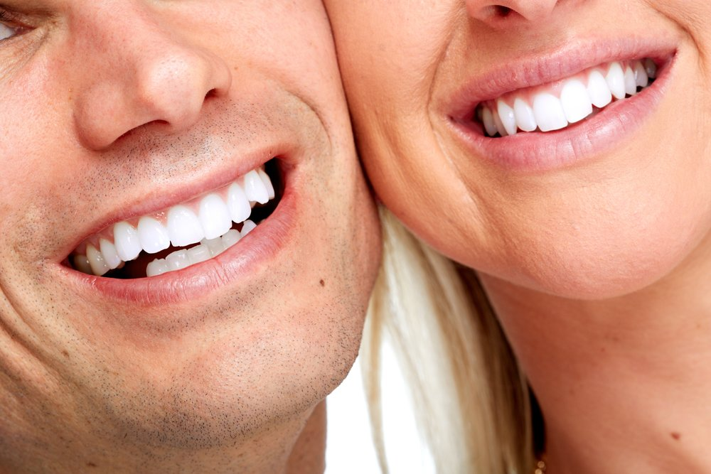 man and woman smiling with perfect teeth