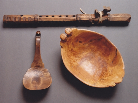 Carved cedar flute, burl effigy bowl, and burl effigy ladle