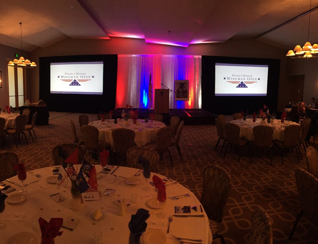 Picture of AV for You Folds of Honor Wingman Open equipment set-up featuring two projectors, two 13' truss towers, with six etc fours lights, and 16' drape behind the stage with 8 up lights set to red, white, and blue.