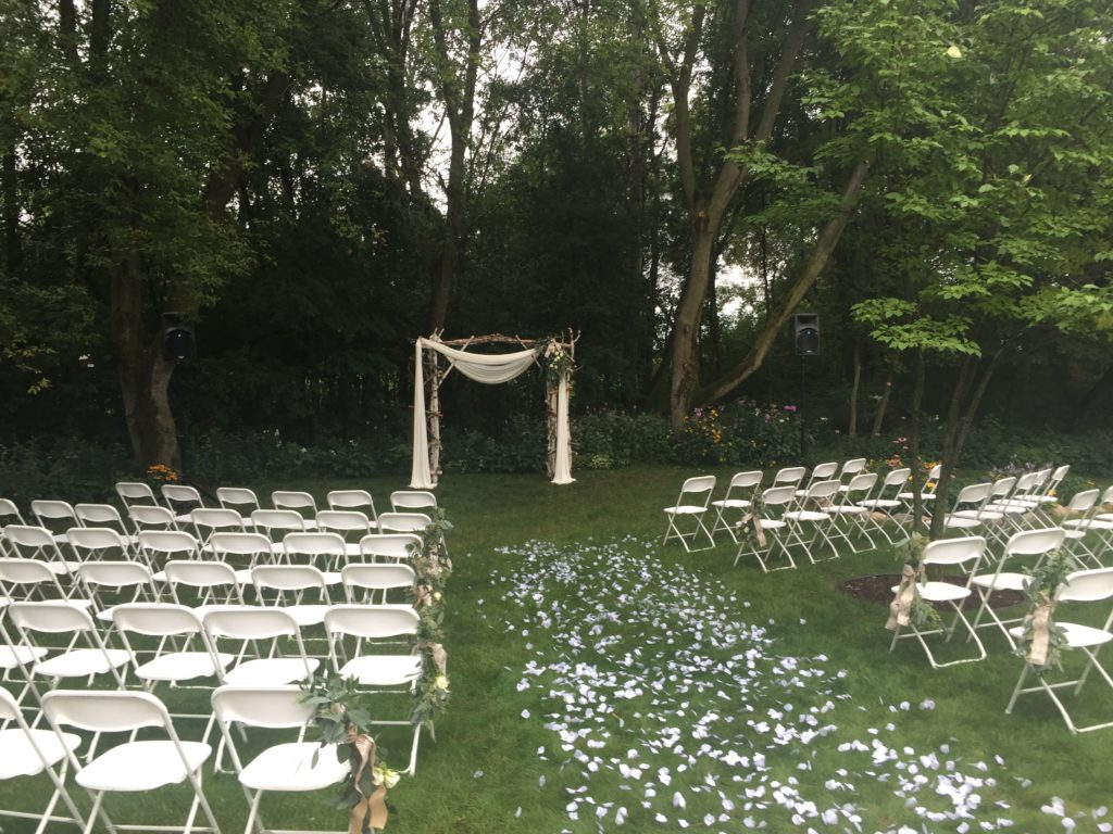 Picture of outdoor wedding with a rose petal aisle, archway, and AV for You speakers