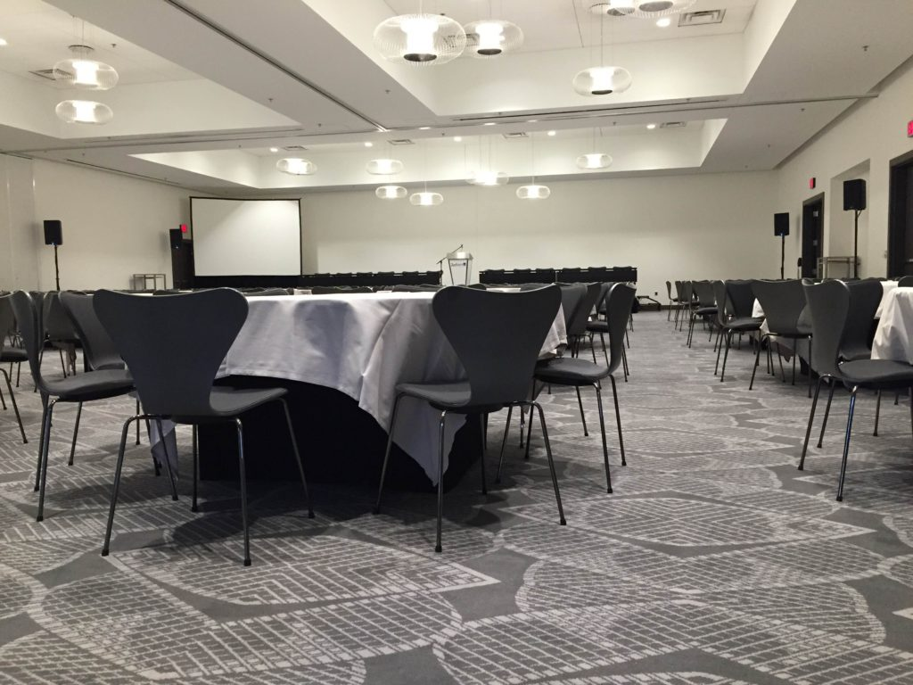 Picture of AV for You Minnetonka Ballroom at the Mall of America Radisson Blu set-up. Pictured equipment includes, our QSC K10 loudspeakers and 2 wireless handheld microphones and a laptop audio input on the podium as well as a 7.5' by 10' fast fold screen.