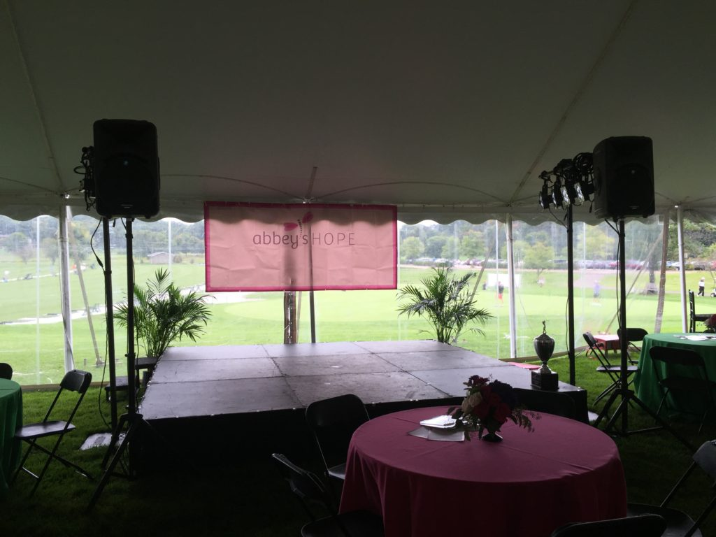 Picture of the stage with an Abbey's Hope banner and AV for You lighting and speakers