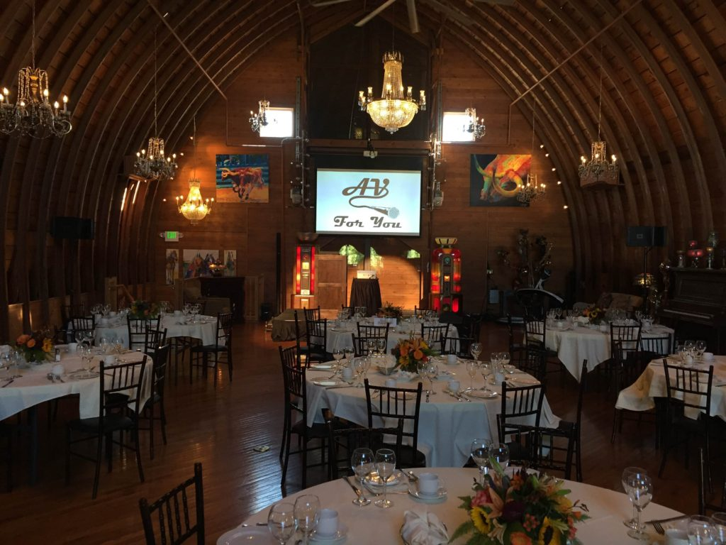 Picture of the interior of the Green Acres Event Center with AV equipment set up.