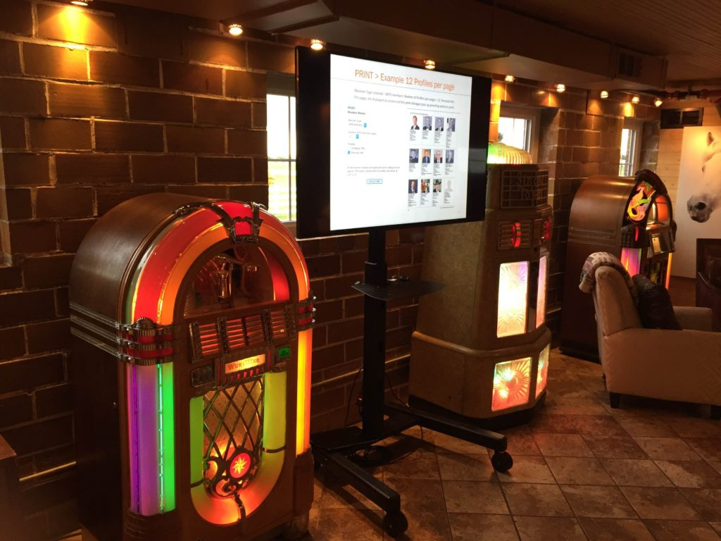 Picture of interior of the Green Acres event center showing multiple jukeboxes and an AV for You monitor on a portable stand.