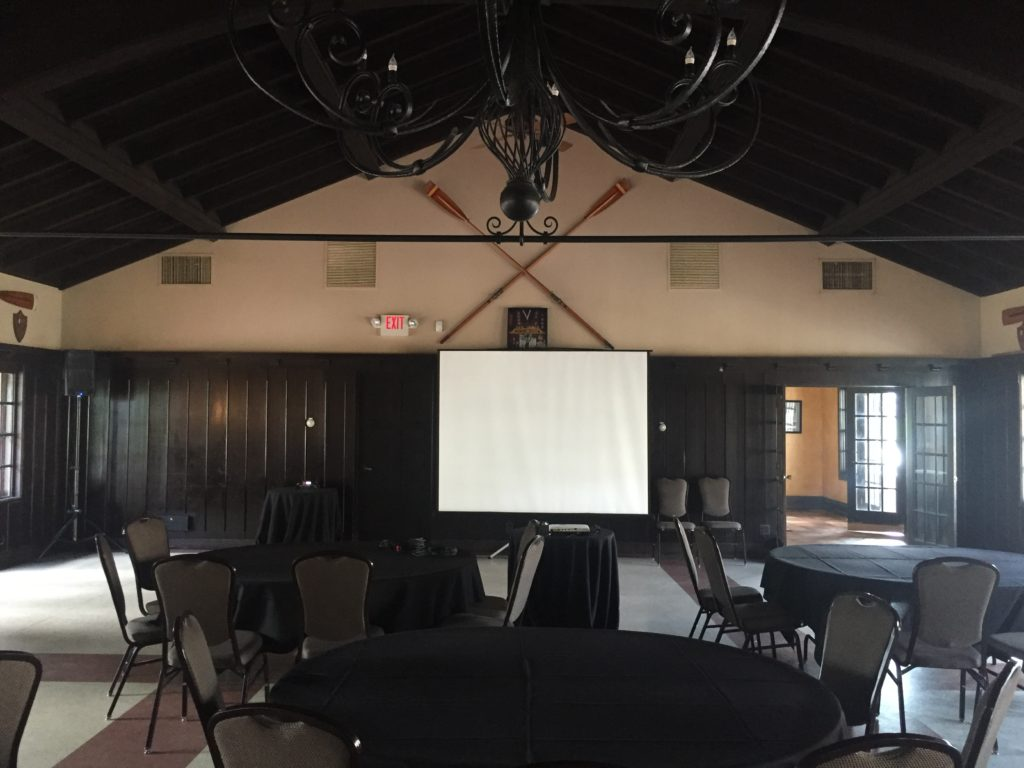 Picture of AV for You audio and video for an event at the Minnesota Boat club. The equipment included one K10 speaker, a handeld wirless microphone, and a projector.