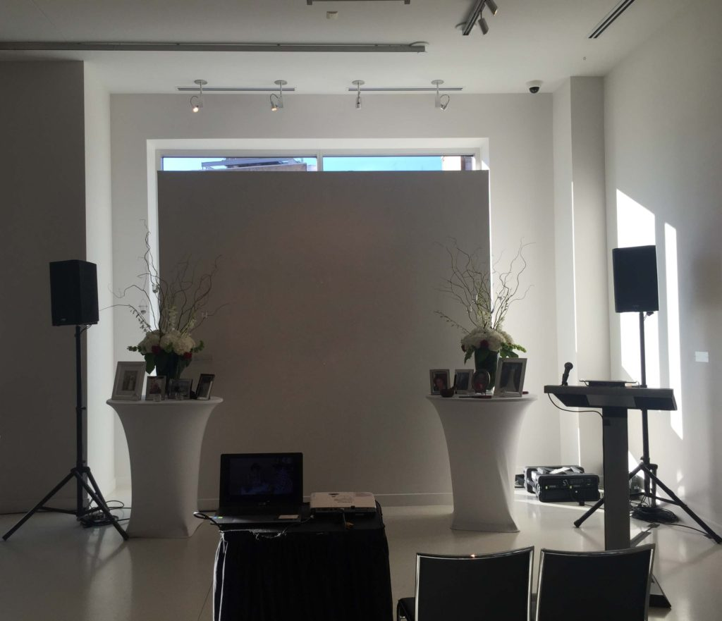 Picture of AV for You audio visual equipment set-up for a wedding at Le Meridien Chambers Minneapolis. Picture shows AV for You two k10s speakers with stands, a 4 channel mixer, 2 lavalier mics, a wired mic, and a 3k projector with stand and laptop.