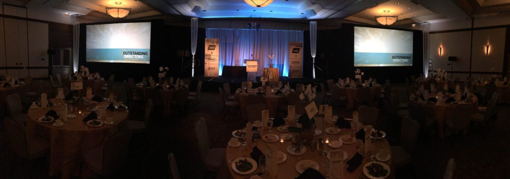 Picture of AV for You rental for the Outstanding Directors Awards at Hyatt Regency. Picture includes two screens and a frosted podium
