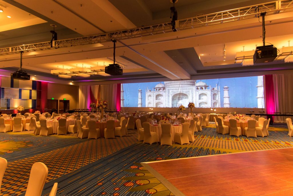 Picture of AV for AV for You Wedding AV rental Minneapolis Marriott City Center rental. Picture shows three 12,000 lumen projectors with an image that is blended in one 56'x11' image.