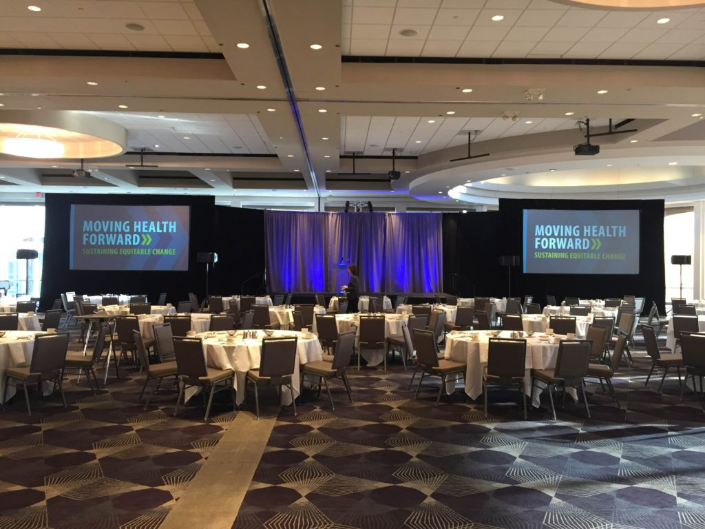 Picture of AV for You Rental Blue Cross Blue Shield Minnesota Luncheon at Intercontinental Hotel set-up featuring a stage and two Dalite Fastfold Screens