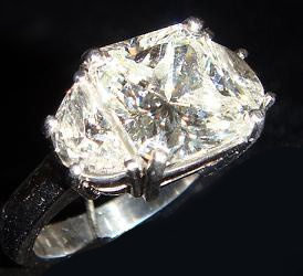 - 3.2 carat radiant cut diamond set with matching moon stones on either side in platinum.