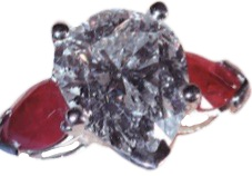 - 3 carat pear shaped center. Enhanced with two .20 pear shaped rubies.