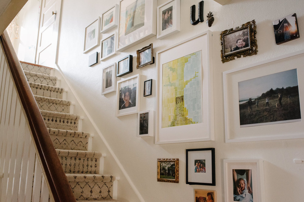 Jess chooses a more eclectic and gathered style of living as shown by her display of frames on her stairwell here.