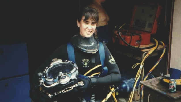 Dominique waits for the final phase of gear up before entering the diving well at Santa Barbara City College. Surface-to-diver communication equipment can be seen in the background (orange box). Tenders constantly monitor divers underwater using hardline communication.